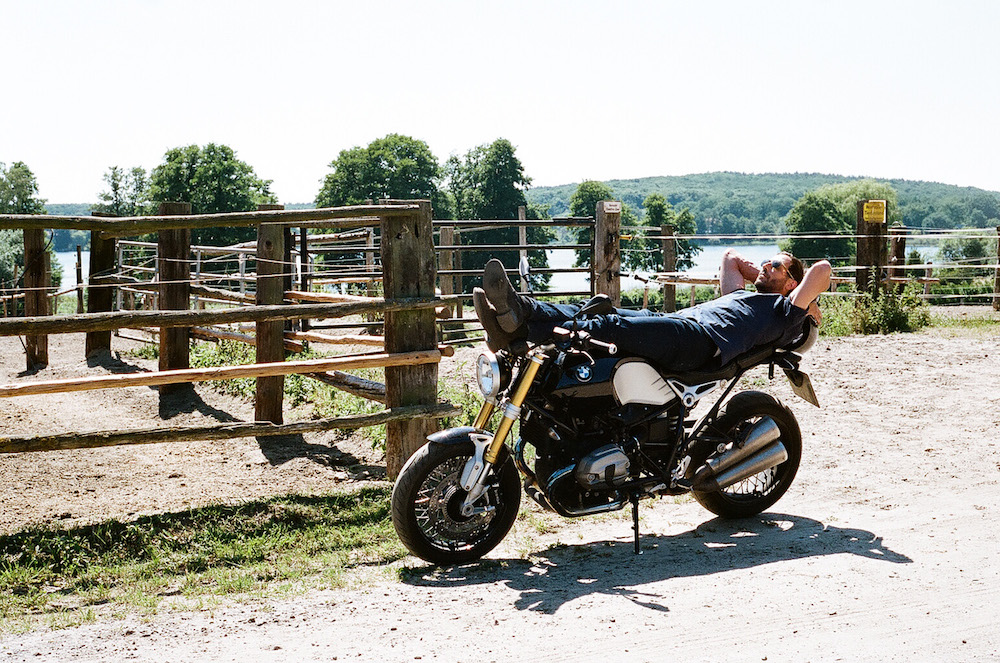 photo, photos, photography, photographer, photographers, motorcycle, motorcycles, flash, daylight, man, men, lounge, dirt, gravel, grass, fence, fences, lake, tree, trees, buildings