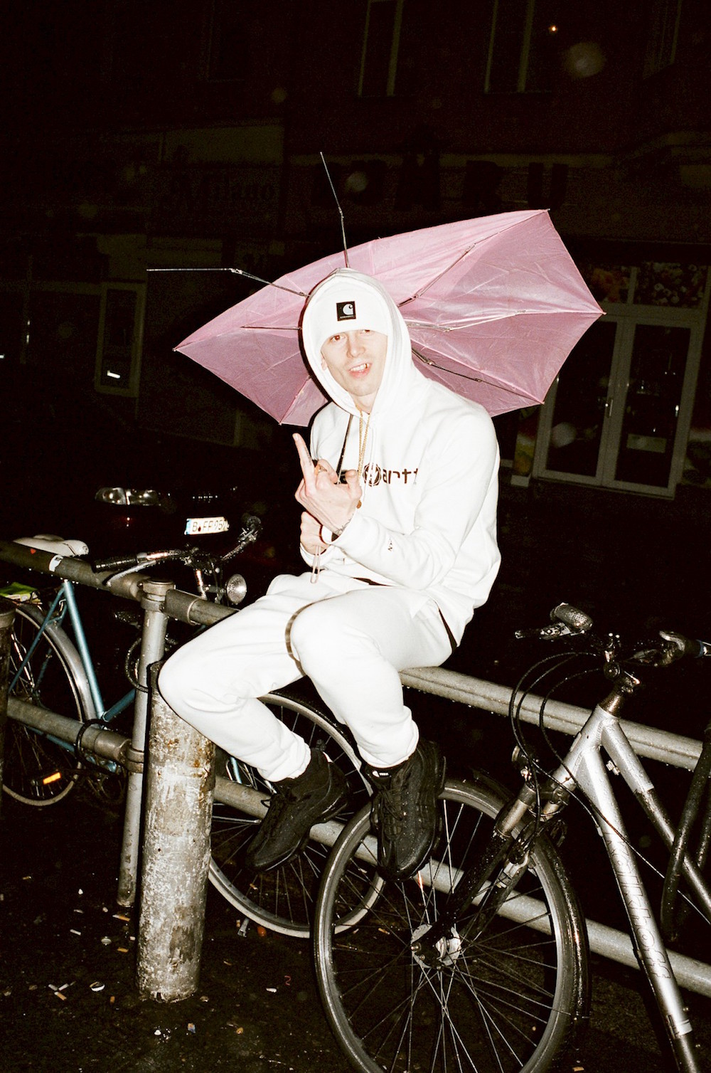 photo photos photography photgrapher photographers man boy street gold chain earring beanie cap streetwear flash pale sweatshirt umbrella rain raining bike bicycle bicycles middle finger