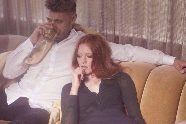 man woman couple drink couch sit lie lying relax rest think thinking ginger covered chain velvet yellow