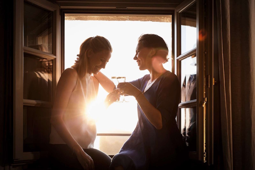 friends women woman laugh laughing talking drink drinking cheers window sun sunny warm