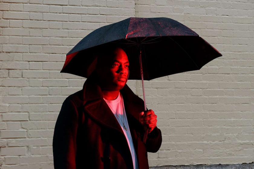 photograph photographer photo photographers photography man stand standing red light umbrella black bricks brick wall white
