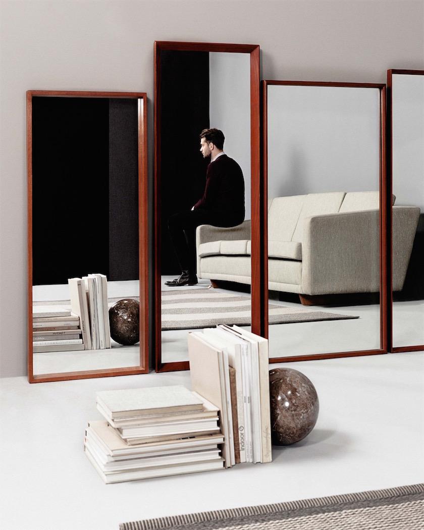 interiors mirror man sitting couch books