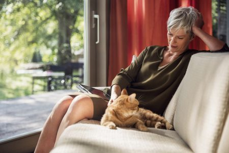 "photo photos photography photographer photographers woman old mature cat sit sitting blurry cat red ipad tablet livingroom ""living room"" sun sunny garden couch grey ""grey hair"" pet animal animals"