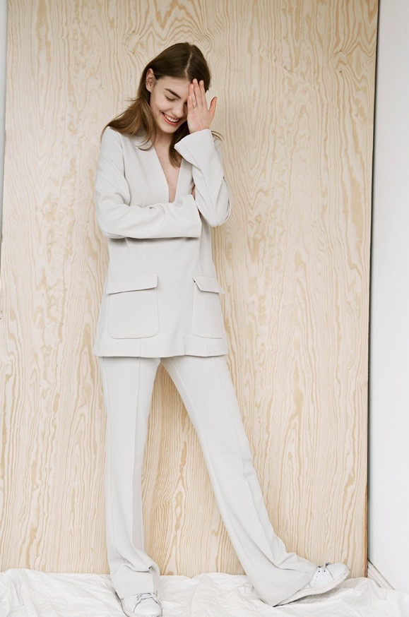 photo, photos, photography, photographer, photographers, woman, women, stand, standing, wood panel, wood grain, white wall, editorial, pose, posing, smile, smiling, editorial, suit, white suit, brunette