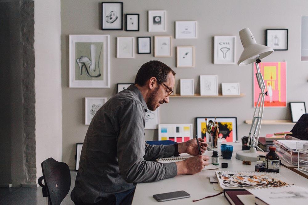 painting painter illustrator drawing artist atelier studio sitting desk desktop man lamp frames