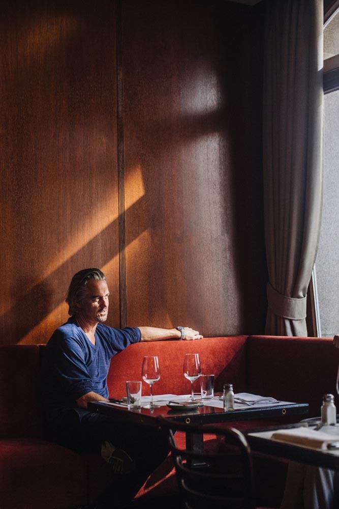 Lifestyle Portrait man sun light table sitting restaurant
