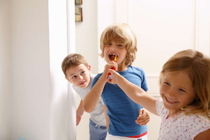 photography, colour image, indoors, front view, waist up, head and shoulders, selective focus, three people, elementary age, boys, girls, 8-9 years, Caucasian appearance, casual clothing, blonde hair, morning, routine, daily life, toothbrush, snatching, fun, dental equipment, brushing teeth, smiling, care, hygienic, bathroom, childhood, lifestyle, domestic life, preparation, brushing, dental hygiene, domestic bathroom, everyday scene, healthcare and medicine, positive emotion, togetherness, friends, friendship, missing teeth, standing, toothy smile, happiness, ecstatic, candid, charming, healthy lifestyle, protection, mouth open, peeking, curiosity