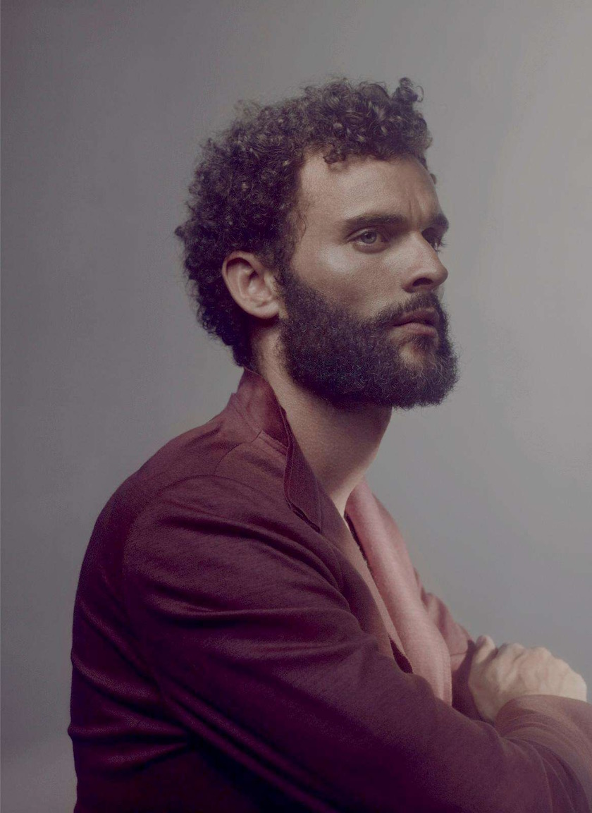 man curly face beard hair sit sitting profile sit sitting