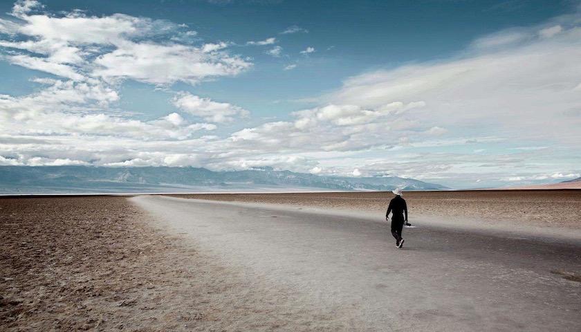 man walking empty alone desert sky clouds path