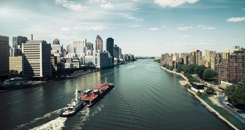 cityscape city buildings river bridge clouds sun sunny sky bright light ship