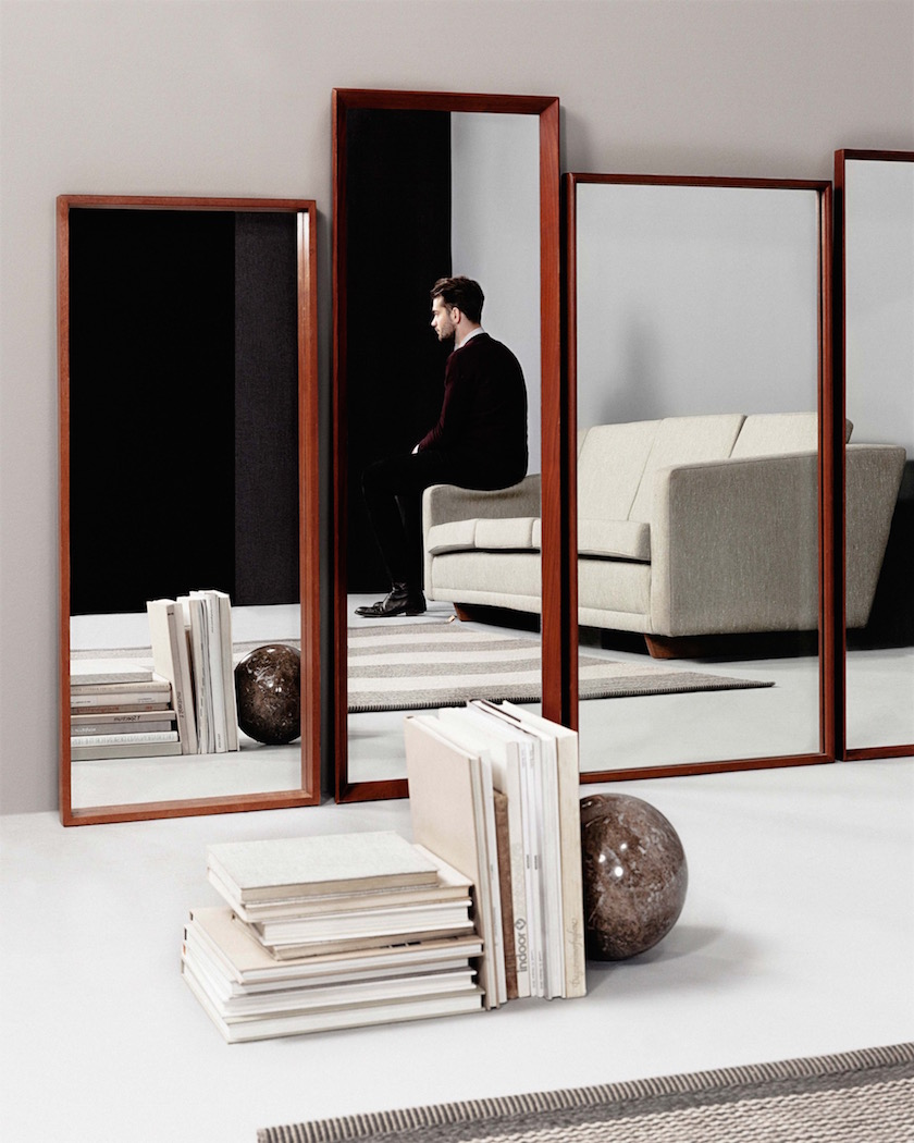 interiors mirror man sitting couch books