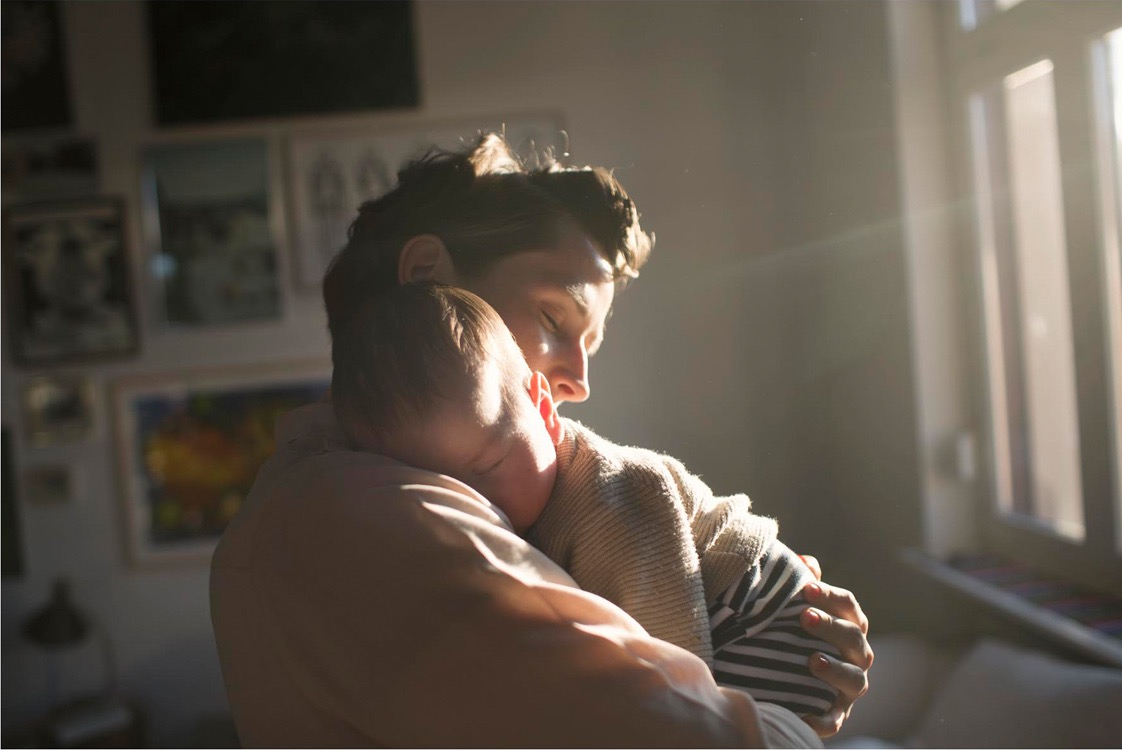 photo, photos, photography, photographer, photographers, woman, women, parent, parents, child, children, infant, hold, holding, embrace, eyes closed, intimate, love, happy, happiness, window, home, sunlight, mother